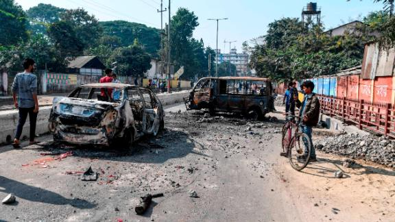 People walk past the remains of gutted vehicles on a road in Guwahati on December 13, 2019, a day after protests against the government's Citizenship Amendment Bill (CAB) broke out across India's northeastern state of Assam. - Internet access has been cut in India's northeastern city of Guwahati after violent protests over a new citizenship law saw two demonstrators shot dead by police, authorities said on December 13. (Photo by Sajjad  HUSSAIN / AFP) (Photo by SAJJAD  HUSSAIN/AFP via Getty Images)
