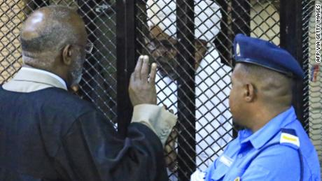 Ousted Sudan President, Omar al-Bashir, sits in a defendant's cage Saturday.