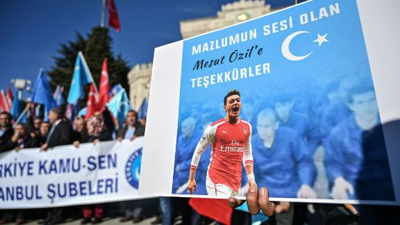 "A supporter of China's Muslim Uyghur minority holds a placard of Arsenal's Turkish origin German midfielder Mesut Ozil reading ""Thanks for being our voice"" past flags of East Turkestan during a demonstration at Beyazid square in Istanbul on December 14, 2019. - Arsenal's Mesut Ozil, a German footballer of Turkish origin, expressed on December 14, 2019 support for Uyghurs in Xinjiang and criticised Muslim countries for their failure to speak up for them. (Photo by Ozan KOSE / AFP) (Photo by OZAN KOSE/AFP via Getty Images)"