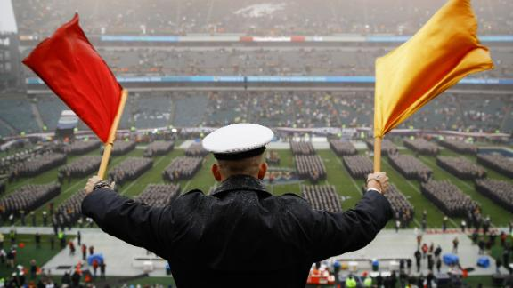 A Navy Midshipman signals his classmate on the field ahead of an NCAA college football game between the Army and the Navy, Saturday, Dec. 14, 2019, in Philadelphia.