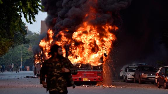 A bus is seen on fire following a demonstration in New Delhi on Sunday, December 15.
