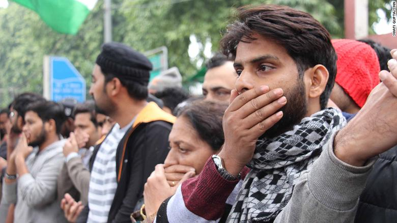 Protesters gather outside Jamia Milia Islamia University in India on Monday, covering their mouths to signify the loss of free speech in the country.