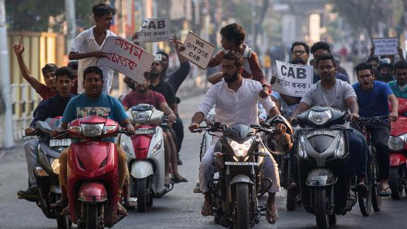 Protesters on motorbikes hold placards during a protest against the bill in Guwahati on Tuesday, December 10.