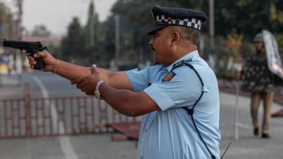 An Indian police officer aims his gun before firing toward protesters who threw stones in Guwahati on December 12.