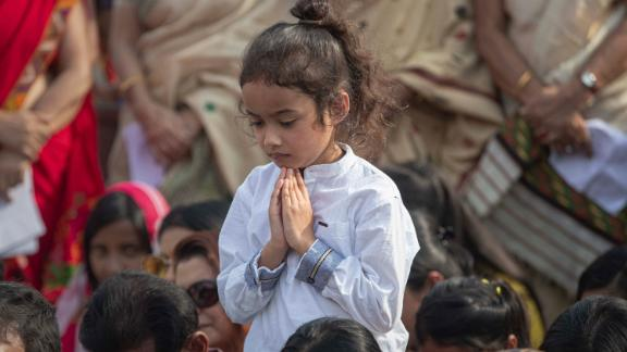 A child prays during a condolence event in Guwahati, India, for demonstrators killed in anti-CAB protests.