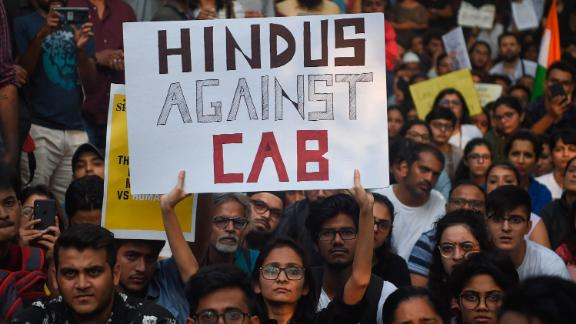 Demonstrators hold signs at the University of Mumbai.