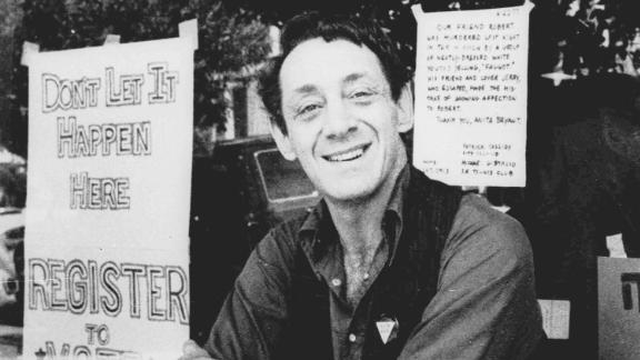 In this 1977 photo, Harvey Milk poses in front of his camera shop in San Francisco.