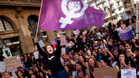 A woman waves a feminist flag as student protesters shout slogans during a demonstration marking International Women's Day in Barcelona on March 8, 2019. - Unions, feminist associations and left-wing parties have called for a work stoppage for two hours on March 8, hoping to recreate the strike and mass protests seen nationwide to mark the same day in 2018. (Photo by Pau Barrena / AFP)        (Photo credit should read PAU BARRENA/AFP via Getty Images)