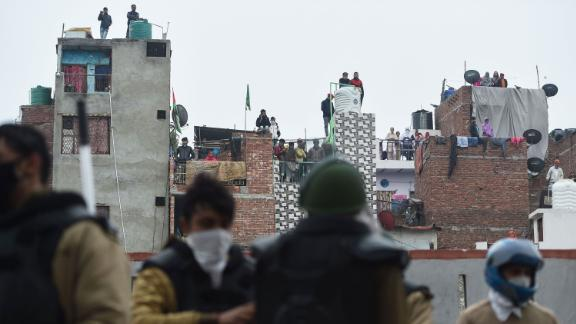 People standing on roofs in New Delhi watch police gathered next to a demonstration on December 17.