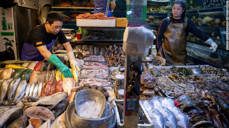 Workers prepare a stall filled with seafood at a market in Beijing on July 10, 2019.