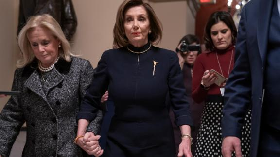 Speaker of the House Nancy Pelosi, D-Calif., holds hands with Rep. Debbie Dingell, D-Mich., as they walk to the chamber where the Democratic-controlled House of Representatives begins a day of debate on the impeachments charges against President Donald Trump for abuse of power and obstruction of Congress, at the Capitol in Washington, Wednesday, Dec. 18, 2019.