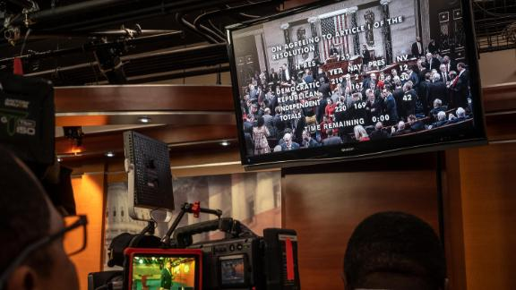 TV crews at the Capitol watch a live feed of the House votes.