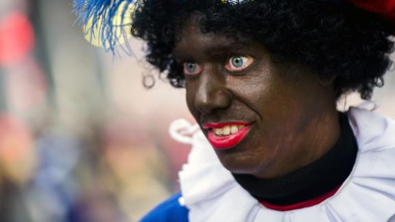 A woman dressed as Zwarte Piet (Black Piet) takes part in the arrival of Sinterklaas (Saint Nicolas) during the traditional move-in 'Intocht Sinterklaas' event in Groningen, Netherlands, on November16,  2013. Zwarte Piet is the companion of Saint Nicolas during a yearly feast celebrated on the evening of 5 December. It was announced in October 2013 that the United Nations, under the authority of the High Commissioner for Human Rights, were to investigate whether Zwarte Piet is a racist stereotype. AFP PHOTO/ANP REMKO DE WAAL netherlands out         (Photo credit should read REMKO DE WAAL/AFP via Getty Images)