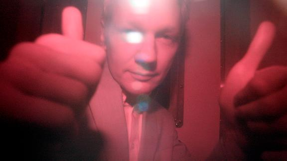 WikiLeaks founder Julian Assange reacts behind the heavily tinted window of a police van as he arrives at Wandsworth Prison in London, in 2010.