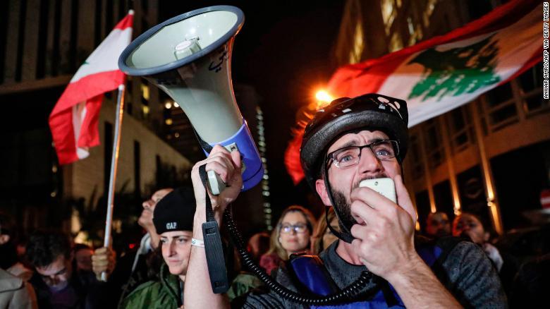 A Lebanese protester speaks into a megaphone on December 16 as demonstrators gather near the home of caretaker Prime Minister Saad Hariri in Beirut.