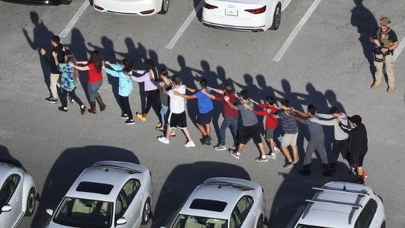 People are brought out of the Marjory Stoneman Douglas High School after a shooting at the school that reportedly killed 17 people on February 14, 2018 in Parkland, Florida.
