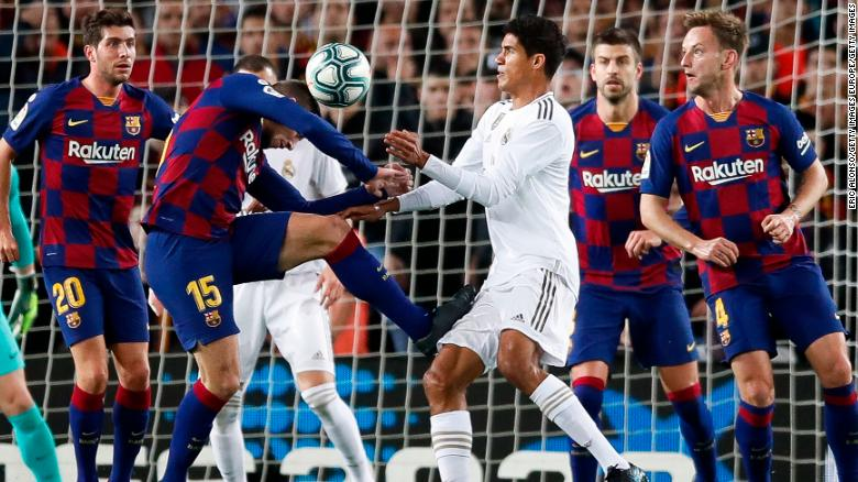 Raphael Varane is challenged by Clement Lenglet.