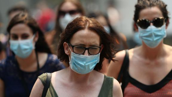 People are seen wearing face masks to protect against the poor air quality in Sydney on December 5.