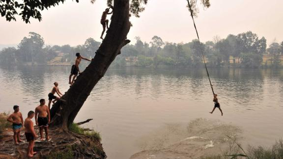 Children swing into the Penrith river during a heatwave in Sydney on December 19.