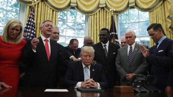 U.S. President Donald Trump, Vice President Mike Pence and faith leaders say a prayer during the signing of a proclamation in the Oval Office of the White House September 1, 2017 in Washington, DC.