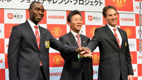 Reigle (right) poses in Tokyo with the former Manchester United striker Andy Cole (left) and the president of the Japanese food company Kagome, Hidenori Nishi (center).