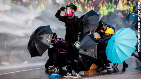 Pro-democracy protesters react as police fire water cannons outside the government headquarters in Hong Kong on September 15, 2019. - Hong Kong riot police fired tear gas and water cannons on September 15 at hardcore pro-democracy protesters hurling rocks and petrol bombs, in a return to the political chaos plaguing the city. (Photo by Isaac LAWRENCE / AFP) (Photo by ISAAC LAWRENCE/AFP via Getty Images)