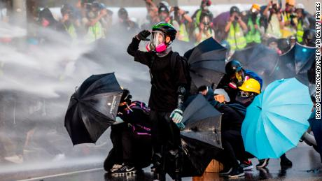TOPSHOT - Pro-democracy protesters react as police fire water cannons outside the government headquarters in Hong Kong on September 15, 2019. - Hong Kong riot police fired tear gas and water cannons on September 15 at hardcore pro-democracy protesters hurling rocks and petrol bombs, in a return to the political chaos plaguing the city. (Photo by Isaac LAWRENCE / AFP) (Photo by ISAAC LAWRENCE/AFP via Getty Images)