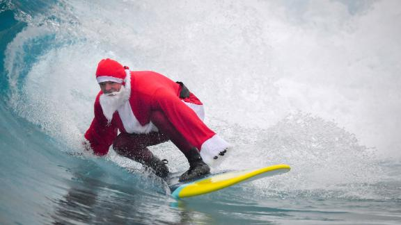 Father Christmas, as Santa Claus is known to Australian kids, is sometimes known surf in on Christmas day at the beach.