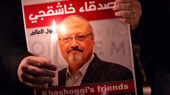 TOPSHOT - A demonstrator holds a poster picturing Saudi journalist Jamal Khashoggi and a lightened candle during a gathering outside the Saudi Arabia consulate in Istanbul, on October 25, 2018. - Jamal Khashoggi, a Washington Post contributor, was killed on October 2, 2018 after a visit to the Saudi consulate in Istanbul to obtain paperwork before marrying his Turkish fiancee. (Photo by Yasin AKGUL / AFP)        (Photo credit should read YASIN AKGUL/AFP via Getty Images)