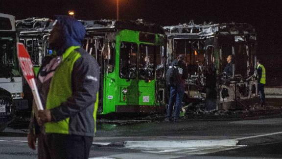 Investigators work at the scene of a fire that destroyed two passenger buses and damaged a third at Los Angeles International Airport.