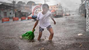 A resident clears garbage floating in a flooded highway during the onslaught of Typhoon Kammuri on December 3, 2019 in Lipa town, Batangas province, Philippines.
