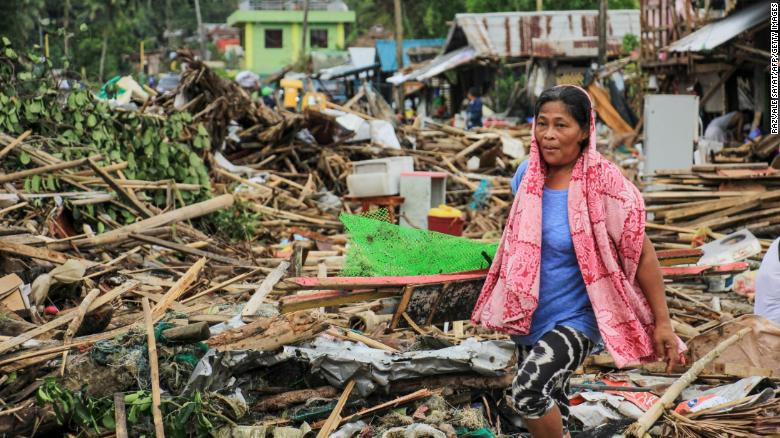 A resident walks past debris from her destroyed houses after Typhoon Kammuri hit the city of Sorsogon, south of of Manila.