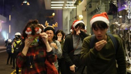 Residents dressed up for the holiday season react to tear gas as police confront demonstrators on Christmas Eve in Hong Kong.