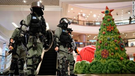 Riot police pass by for Christmas decorations in a mall during a protest on Christmas Eve.