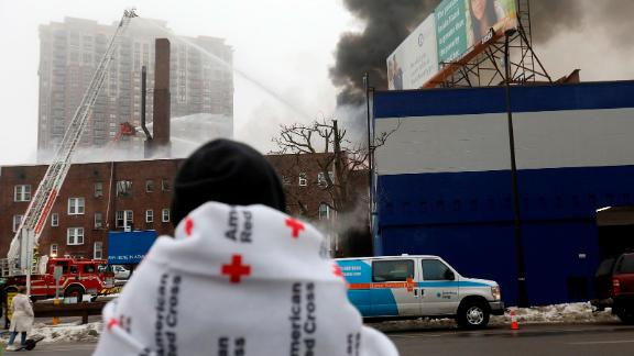 People displaced by the fire wait to hear news on their fate after a four-alarm fire at the Francis Drake Hotel apartments that broke out early Christmas morning.