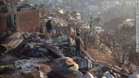 Residents look at the destruction caused by the fires in Valparaiso.