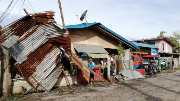 Residents stand next to a house damaged by typhoon Phanfone in Ormoc City, Leyte province in central Philippines.
