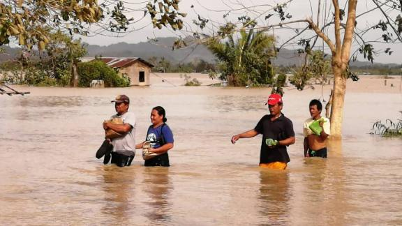 People in Leyte province wade through a flooded highway, caused by heavy rains due to typhoon Phanfone, in Ormoc city.