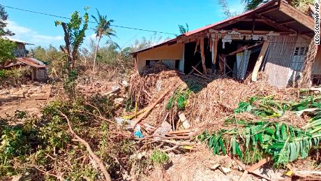 Debris from floods caused by Typhoon Phanfone surround a damaged house in Balasan Town, Iloilo province, central Philippines on Thursday.