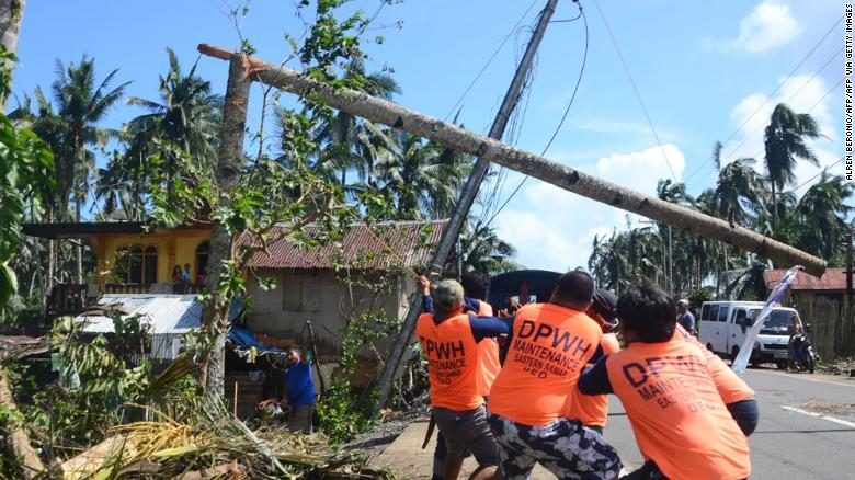 Workers pull a fallen electric pylon damaged at the height of Typhoon Phanfone in Salcedo town in Eastern Samar province on December 26, 2019.