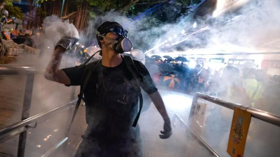 HONG KONG, CHINA - AUGUST 11:  A protester throws back tear gas fired by riot police in the Cheung Sha Wan area on August 11, 2019 in Hong Kong, China. Pro-democracy protesters have continued rallies against a controversial extradition bill since June 9, when the city was plunged into crisis after waves of demonstrations and several violent clashes. While Hong Kong