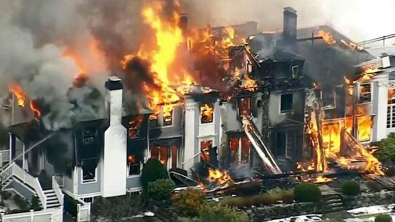 The 6,500-square-foot house was engulfed in flames as firefighters battled to bring it under control.