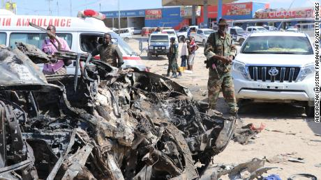 A soldier is seen next to the wreckage of car that was damaged during the suicide attack in Mogadishu on Saturday.