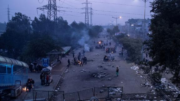 Demonstrators sit next to bonfires during dusk as they block a road during a protest in New Delhi on Sunday, December 22.