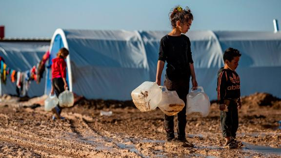 Children carry jugs to fill with water in the Washukanni camp for internally displaced people in northeastern Syria.
