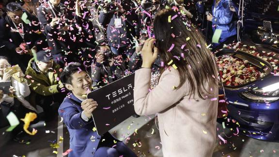 An employee, left, proposes to his girlfriend with his newly delivered Tesla Model 3 in Shanghai on Monday.