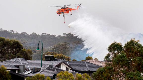 A skycrane drops water on a bushfire burning near houses in Bundoora, Melbourne, on Monday, December 30.
