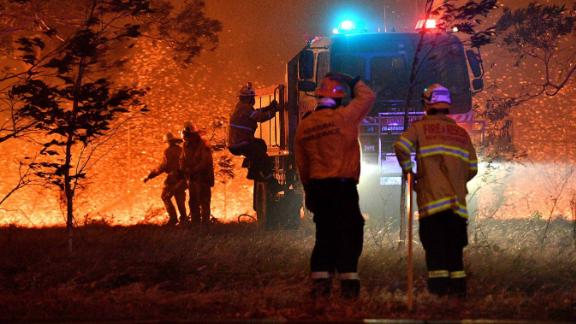 Firefighters hose down trees as they battle against bushfires around the town of Nowra in the Australian state of New South Wales on December 31, 2019. Thousands of holidaymakers and locals were forced to flee to beaches in fire-ravaged southeast Australia on December 31, as blazes ripped through popular tourist areas leaving no escape by land.