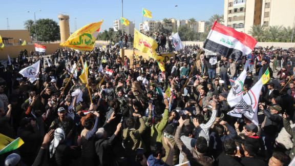 """Several thousand Iraqi protesters, waving national flags and banners of the Hashed al-Shaabi, a mostly Shiite network of local armed groups trained and armed by powerful neighbour Iran, demonstrate outside the US embassy in Baghdad on December 31, 2019, breaching its outer wall and chanting """"Death to America!"""" in anger over weekend air strikes that killed pro-Iran fighters. - It was the first time in years protesters have been able to reach the US embassy in the Iraqi capital, which is sheltered behind a series of checkpoints in the high-security Green Zone. (Photo by AHMAD AL-RUBAYE / AFP) (Photo by AHMAD AL-RUBAYE/AFP via Getty Images)"""