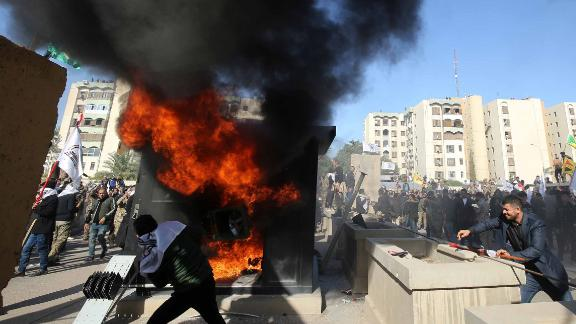 """Iraqi protesters set ablaze a sentry box in front of the US embassy building in the capital Baghdad to protest against the weekend's air strikes by US planes on several bases belonging to the Hezbollah brigades near Al-Qaim, an Iraqi district bordering Syria, on December 31, 2019. - Several thousand Iraqi protesters attacked the US embassy in Baghdad on today, breaching its outer wall and chanting """"Death to America!"""" in anger over weekend air strikes that killed pro-Iran fighters. (Photo by Ahmad AL-RUBAYE / AFP) (Photo by AHMAD AL-RUBAYE/AFP via Getty Images)"""